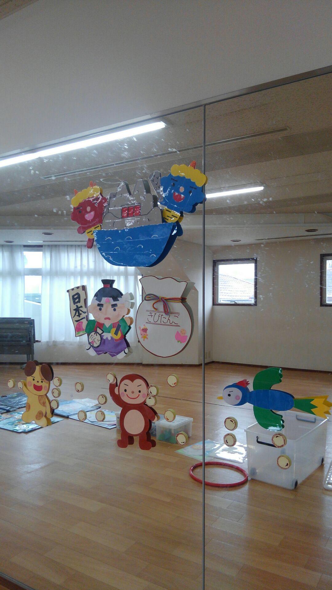 教室壁面の鏡に貼られた装飾イラスト。鬼が島に赤鬼と青鬼。少し離れて桃太郎、猿、犬、きじがきびだんごを持っています。「きびだんご」と書かれた大きな袋のイラストもあります。